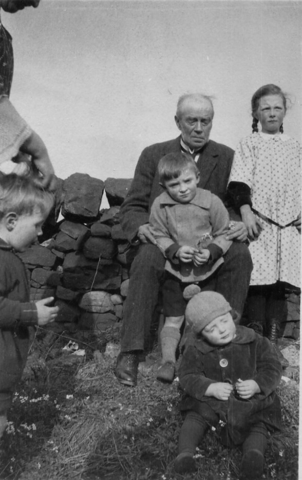 old man on farm wall with four children